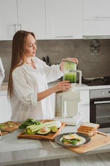 Beautiful young woman preparing healthy green smoothie in her kitchen