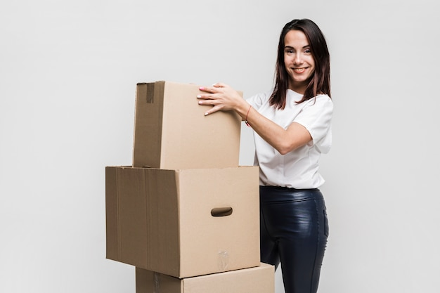 Beautiful young woman preparing moving boxes