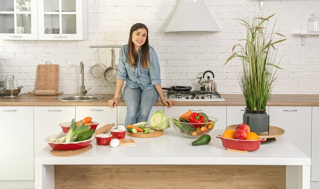 Beautiful young woman preparing a vegetarian salad from various vegetables on the background of the kitchen interior in light colors.