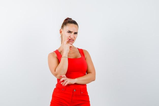 Bella giovane donna appoggiando il mento a portata di mano in canottiera rossa, pantaloni e guardando preoccupato. vista frontale.