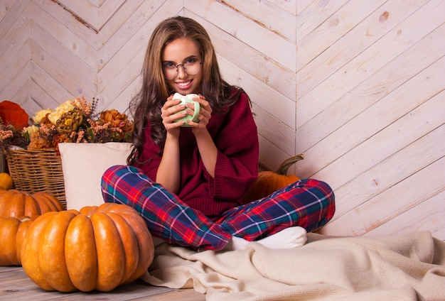 Beautiful young woman and pumpkins, autumn