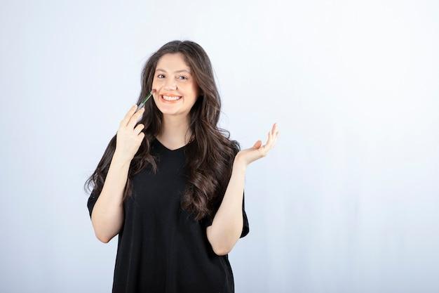 Bella giovane donna che mette arrossire con pennello cosmetico sul muro bianco.