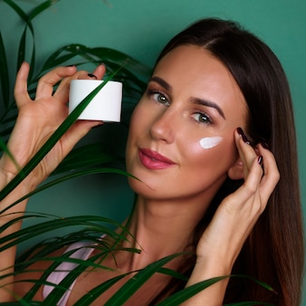 Beautiful young woman putting cream on pure skin between palm leaves on green background