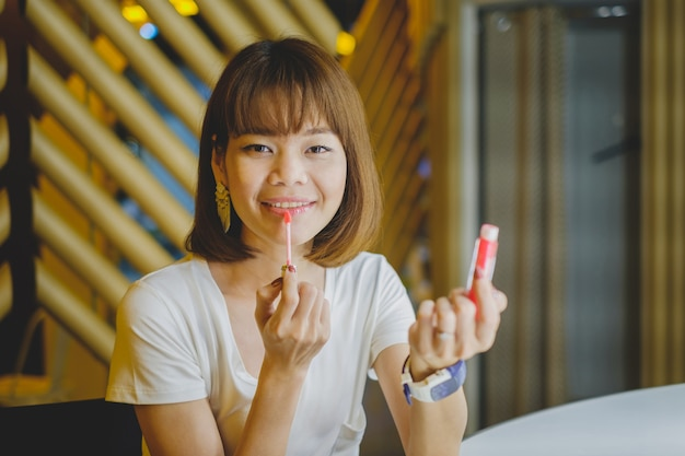 Beautiful young woman putting on red lipstick gloss.