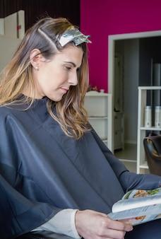머리에 염색약을 바르고 기다리는 동안 잡지를 읽는 아름다운 젊은 여성