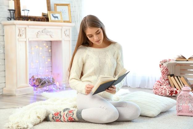 Красивая молодая женщина, читающая книгу дома