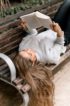 Beautiful young woman reading a book on a bench