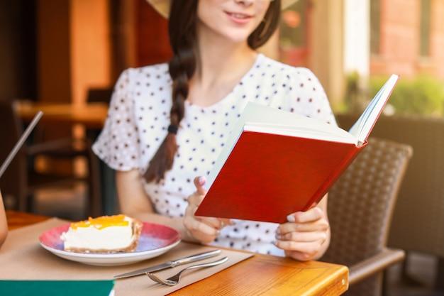 Красивая молодая женщина, читающая книгу в уличном кафе