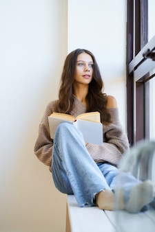 Beautiful young woman reading book and looking out window
