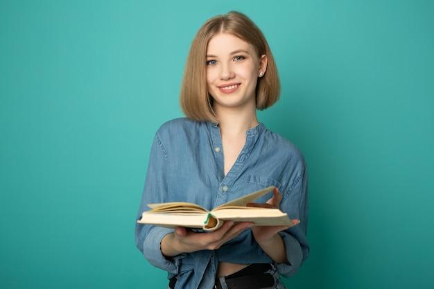 파란색 배경에 책을 읽고 아름 다운 젊은 여자