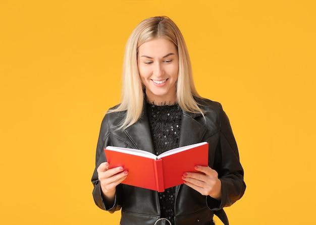 색상 표면에 책을 읽고 아름 다운 젊은 여자