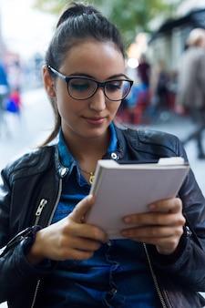 Bella giovane donna che legge un libro in strada.