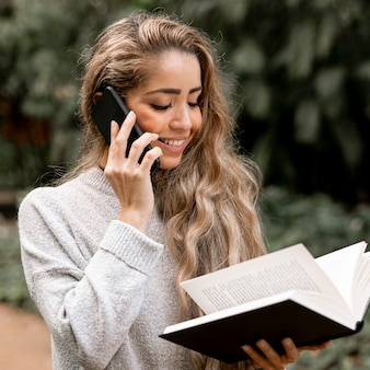 Beautiful young woman reading a book while talking on the phone