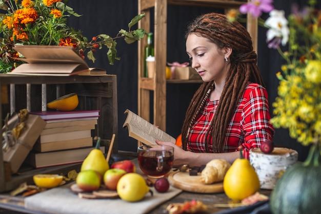 Красивая молодая женщина, читающая романтическую книгу в осенней атмосфере