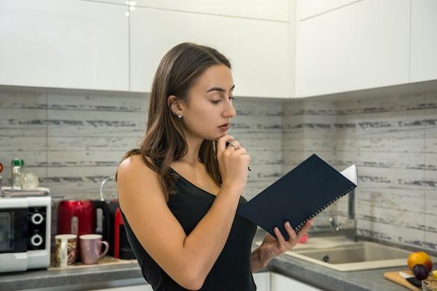 美しい若い女性は、朝食に健康的な食べ物を調理するためにキッチンでノートを読みます。