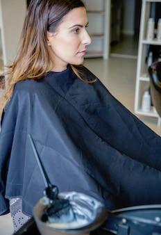 아름 다운 젊은 여자는 그릇에 defocused 머리 염료와 전경에서 브러시로 머리 색깔을 변경할 준비가 되어 있습니다