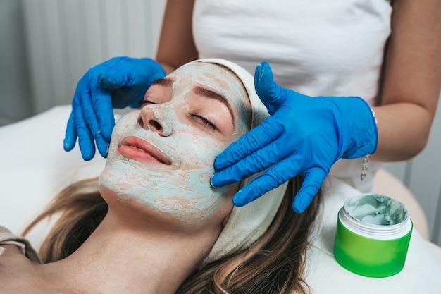 スパビューティーサロンで若返り効果のあるフェイシャルマスクを受けている美しい若い女性。