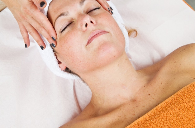 Beautiful young woman receiving facial massage with closed eyes in a beauty center