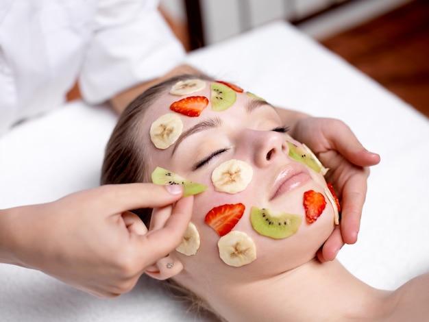 Bella giovane donna che riceve maschera di frutta su una faccia nel salone di bellezza