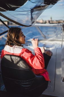 Beautiful young woman in a red cloak drinking champagne on a yacht.