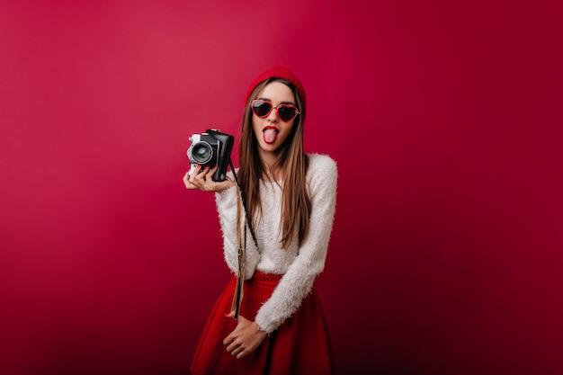 Bella giovane donna in cappello rosso facendo facce buffe mentre posa con la fotocamera