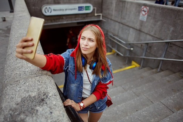 Beautiful young woman in red hoodie is taking selfie using mobile phone near entrance to subway. Premium Photo