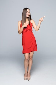 La bella giovane donna in mini abito rosso e tacchi alti è in piedi, presenta qualcosa e distoglie lo sguardo. vista laterale. colpo integrale isolato su bianco.