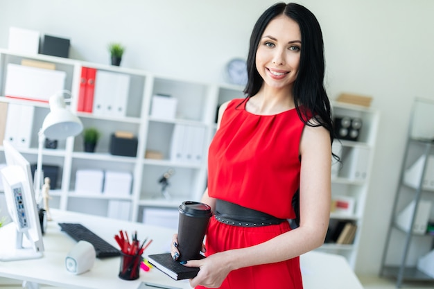 Beautiful young woman in a red suit is standing in the office and is holding a notebook and a glass of coffee.