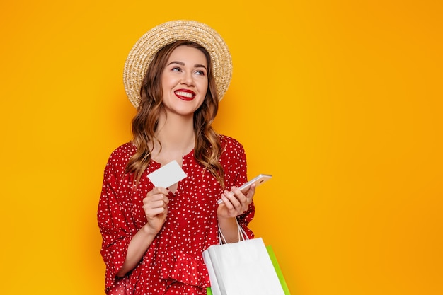 Beautiful young woman in a red summer dress straw hat holds a mobile phone and a credit card in her hands isolated on a yellow wall  mockup web banner. girl makes online purchases
