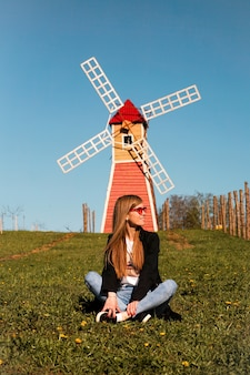 Beautiful young woman in red sunglasses sits on the grass against the backdrop of the red mill.