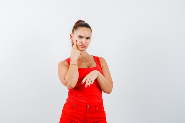 Beautiful young woman in red tank top, pants pointing at her eyelid and looking upset , front view.
