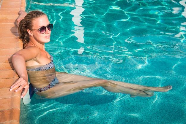 Bella giovane donna rinfrescante alla piscina estiva
