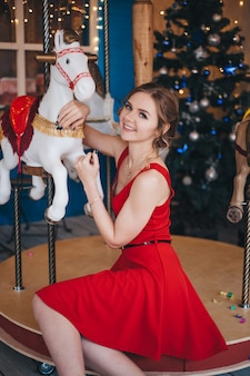 Beautiful young woman rejoices near a carousel with horses. christmas.