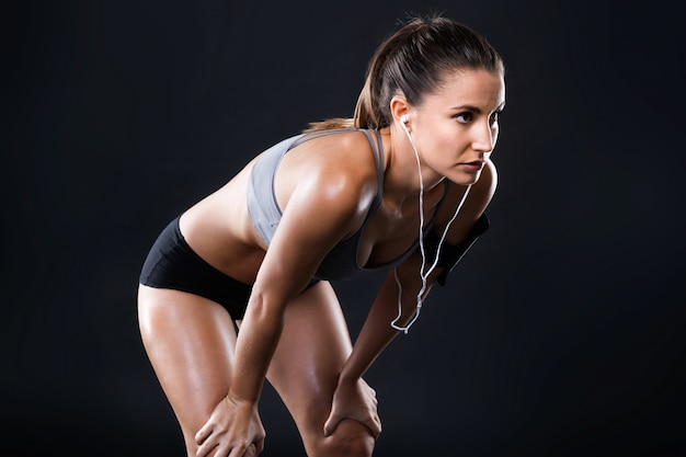 Beautiful young woman relaxing after work out over black background.