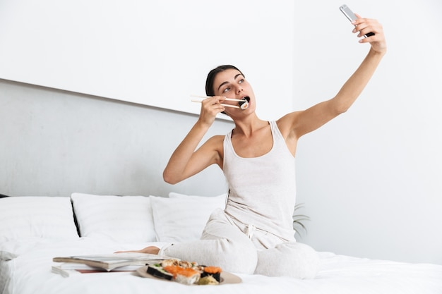Beautiful young woman relaxing on bed at home, eating sushi from a plate, taking a selfie