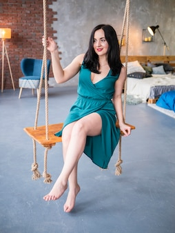 Beautiful young woman relaxing and chilling on a swing in loft living room with brick walls. beautiful legs barefoot on grey floor.