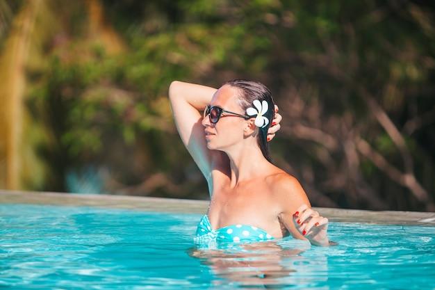 Красивая молодая женщина, расслабляющаяся в бассейне