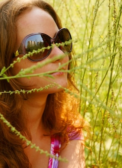 Красивая молодая женщина, расслабляющаяся в траве