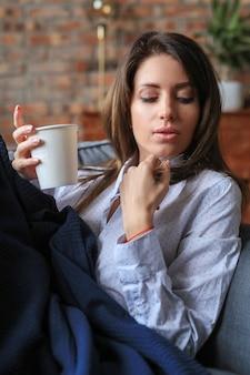 温かい飲み物とソファでリラックスした美しい若い女性
