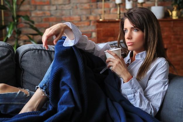 Красивая молодая женщина расслабляется на диване с горячим напитком