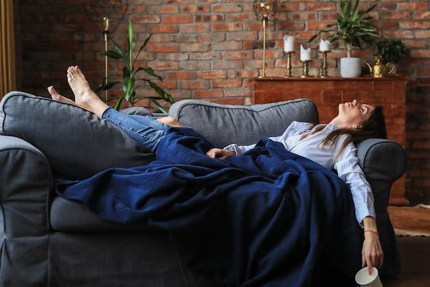 ソファでリラックスした美しい若い女性