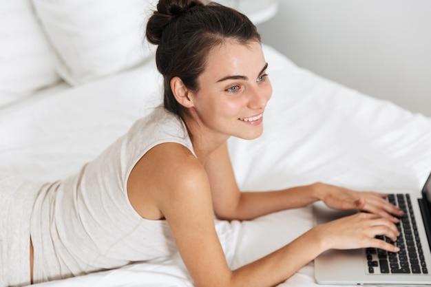 Красивая молодая женщина отдыхает на кровати дома, используя портативный компьютер