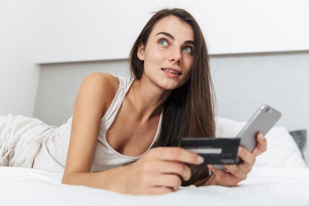 Красивая молодая женщина отдыхает на кровати дома, используя мобильный телефон, держа кредитную карту, делая покупки