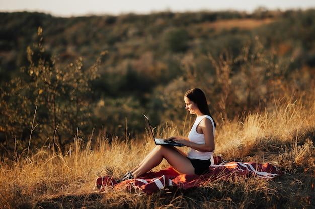 ノートパソコンで草の上でリラックスした美しい若い女性。