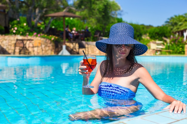 Beautiful young woman relaxing in pool with cocktail