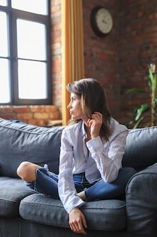 Bella giovane donna che si distende nel divano