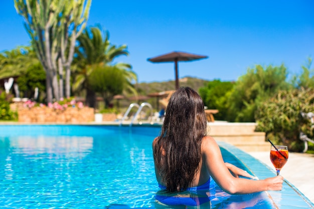 Beautiful young woman relaxing in swimming pool with cocktail
