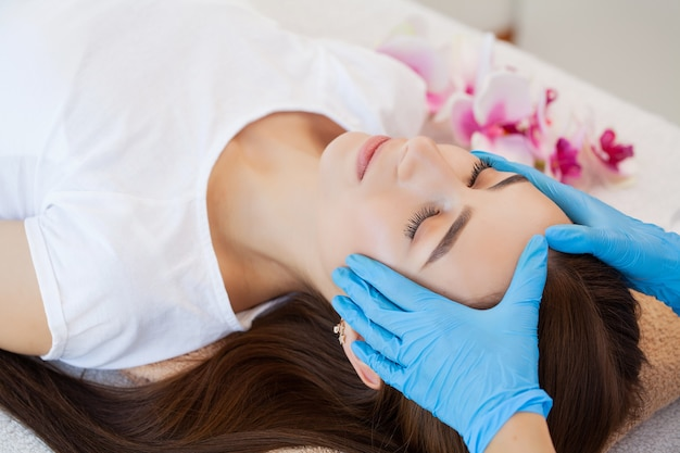Beautiful young woman relaxing with hand massage at beauty spa salon.