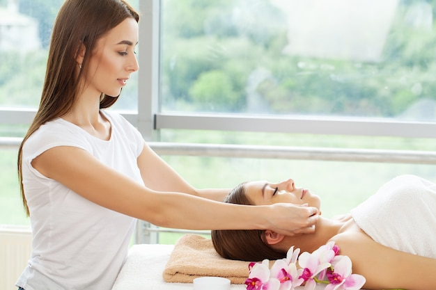 Beautiful young woman relaxing with hand massage at beauty spa salon