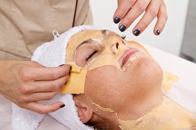 Beautiful young woman remove  facial mask  in a beauty center